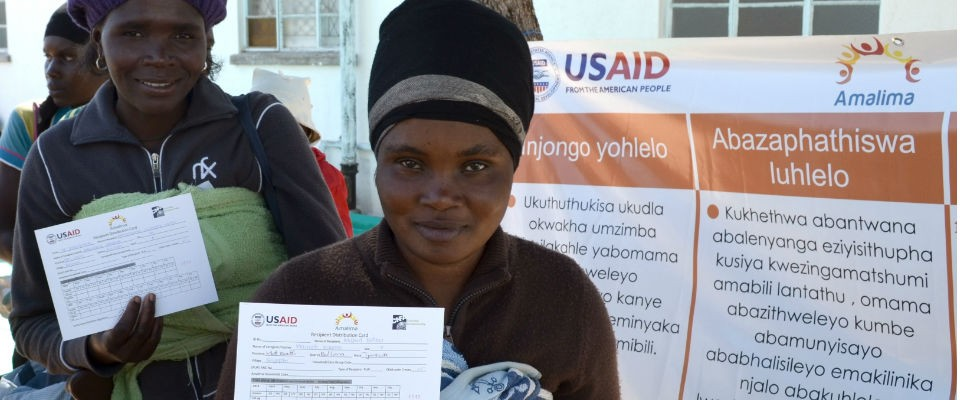 Mothers hold up their ration cards at a distribution site in Matabeleland South Province. USAID provides rations of fortified co