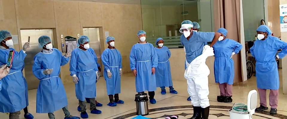 A group of people in medical scrubs and face masks stands in a circle around a person putting on hazmat clothing