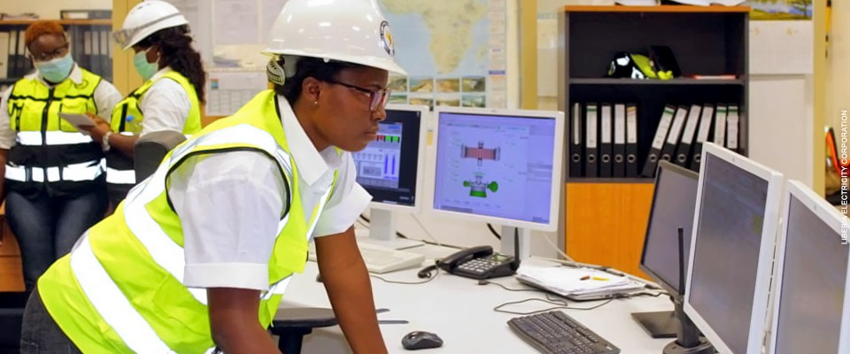 A female engineer works at a control terminal in the operations center of a hydropower plant in Liberia.