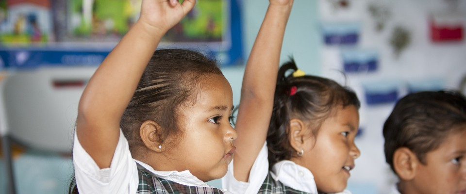 Young girls in Honduras raise their hands in class. USAID/Honduras