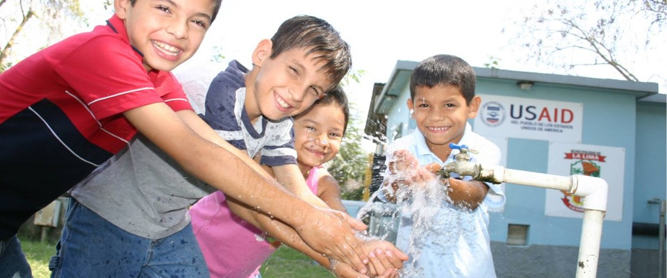 Children playing with water during a water system inauguration in La Lima.