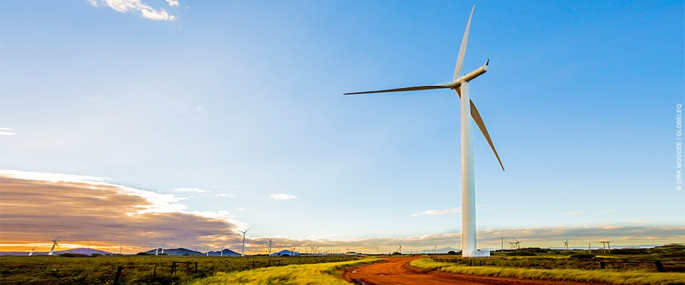 A tall wind turbine dominates the foreground of this photo of a wind farm that stretches across a plain.