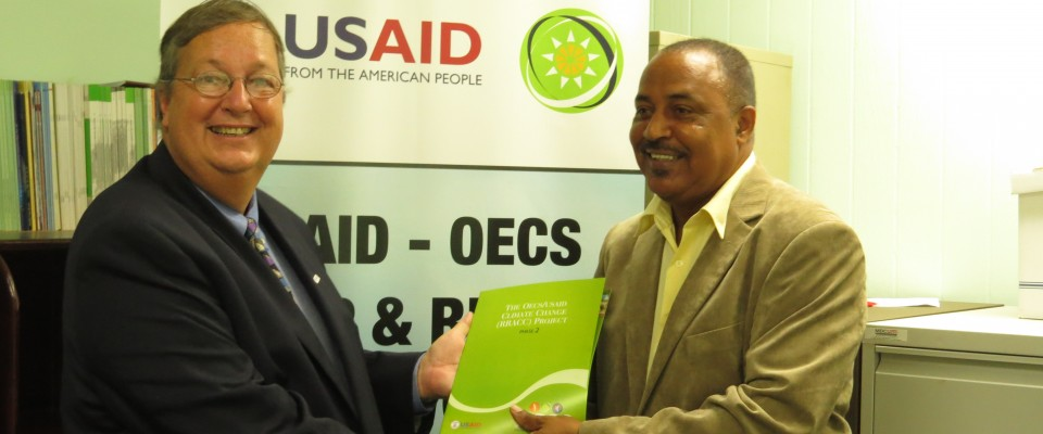 Mission Director Chris Cushing, officially hands over RRACC Demonstration project documents to Alvin DaBreo, Minister with respo
