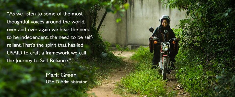 "A woman rides a motorbike in the woods, with a quote from USAID Administrator Mark Green: ""As we listen to some of the most thoughtful voices around the world, over and over again we hear the need to be independent, the need to be self-reliant. That's the spirit that has led USAID to craft a framework we call the Journey to Self-Reliance."""