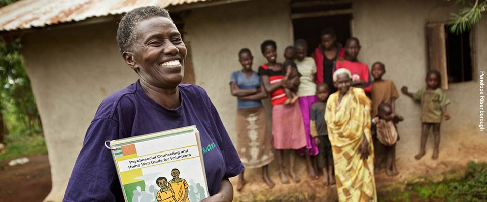 A health volunteer smiles at the camera holding educational material.