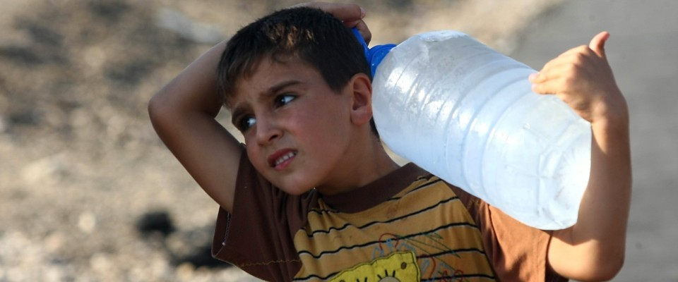 A young boy, a Syrian refugee, carries a container of water in Kilis, Turkey at the border with Syria.