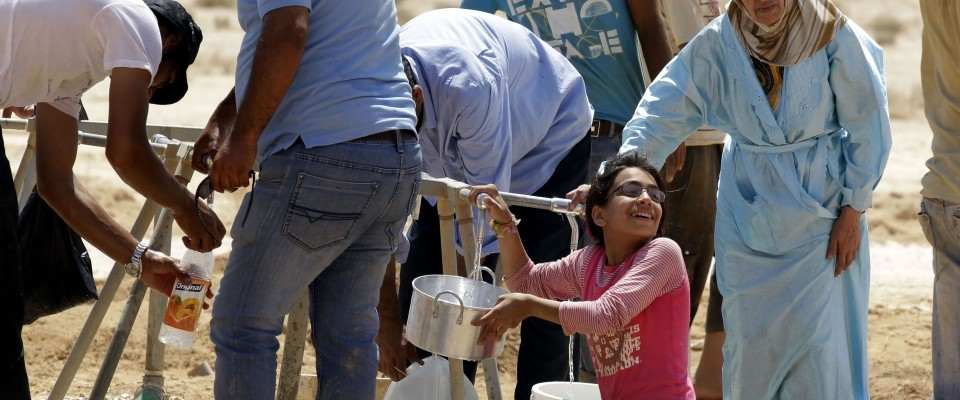 Syrian refugees collecting water at a refugee camp in Jordan near the border with Syria.