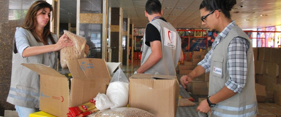 Image of Syrian Red Crescent staff filling boxes of food for internally displaced people.