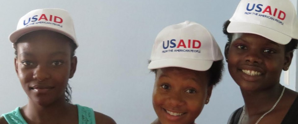 Three youth in USAID hats