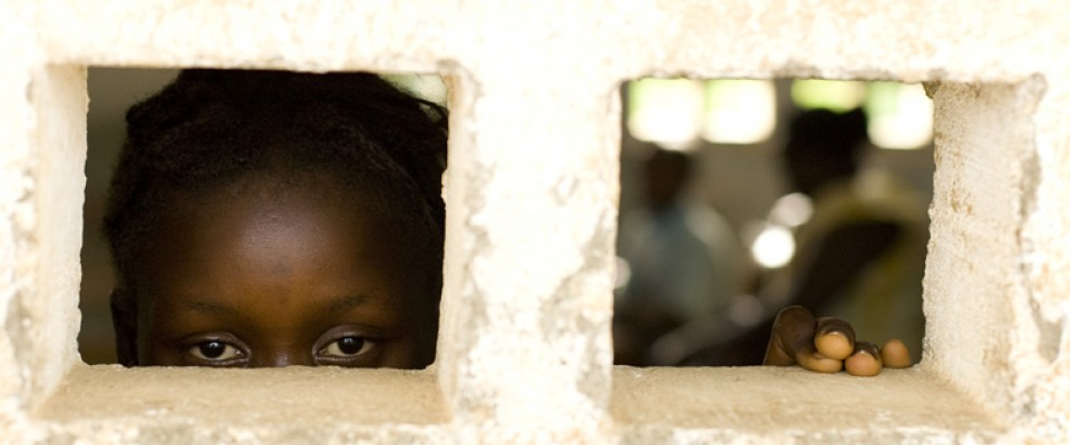 A 13-year-old former sex worker peers out the window of a school in Sierra Leone.