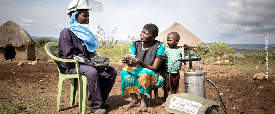 A malaria spray technician speaks with a woman and her son. Photo credit: Jessica Scranton, PMI/AIRS