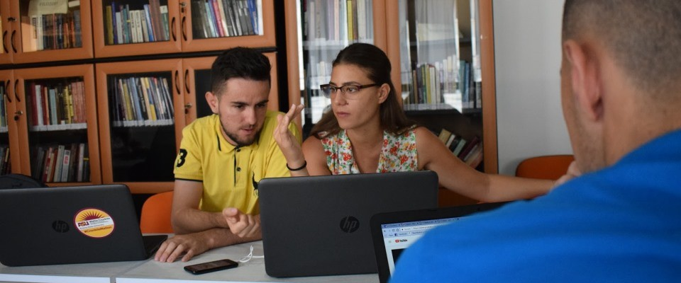 A young man and woman in front of computer laptops