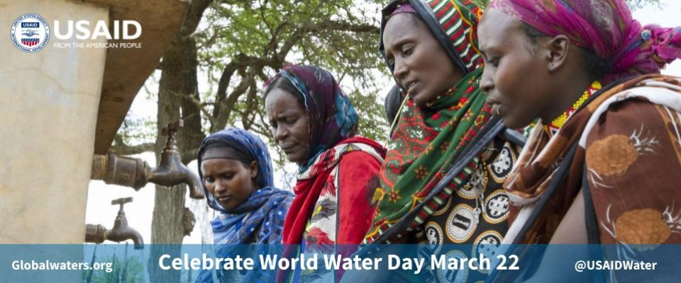 Several women stand near a water station. Celebrate World Water Day on March 22
