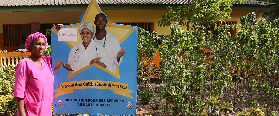 Woman standing next to a Gold Star poster I Photo Credit: Youssouf Bah