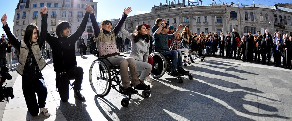 People holding hands, kneeling and in wheelchairs.