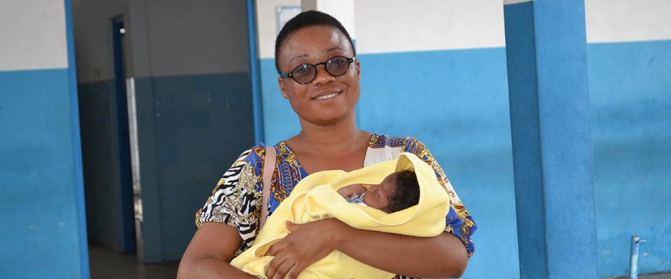 Smiling woman holds her newborn