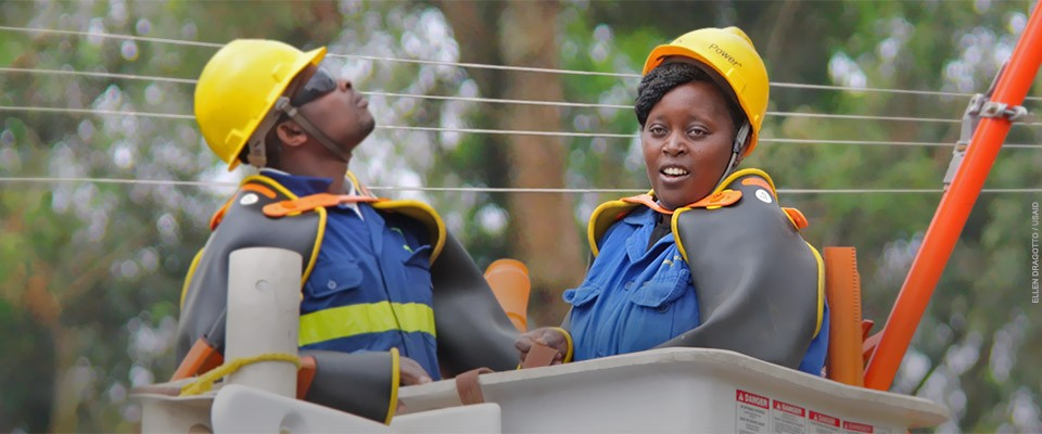 two power line technicians—one male, one female—in their safety gear stand in a lift, preparing to work on power lines during a training exercise