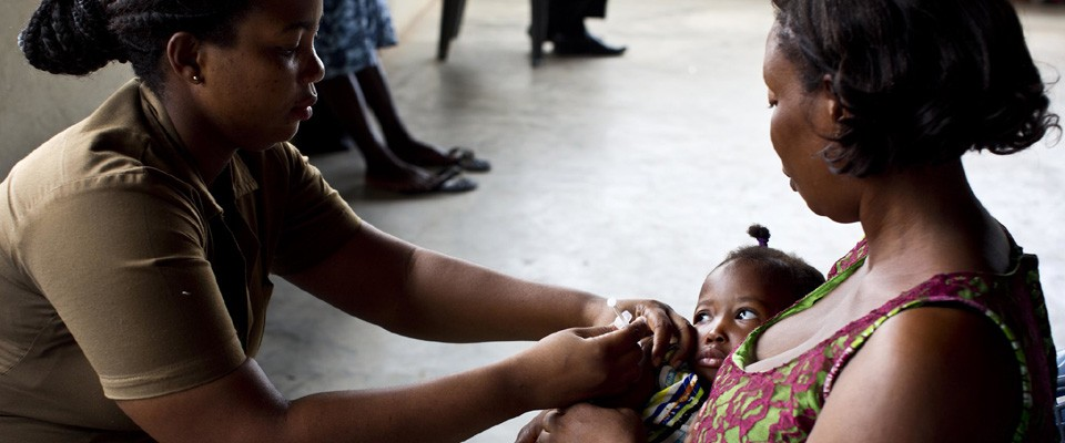 A health care worker administers immunization to a child