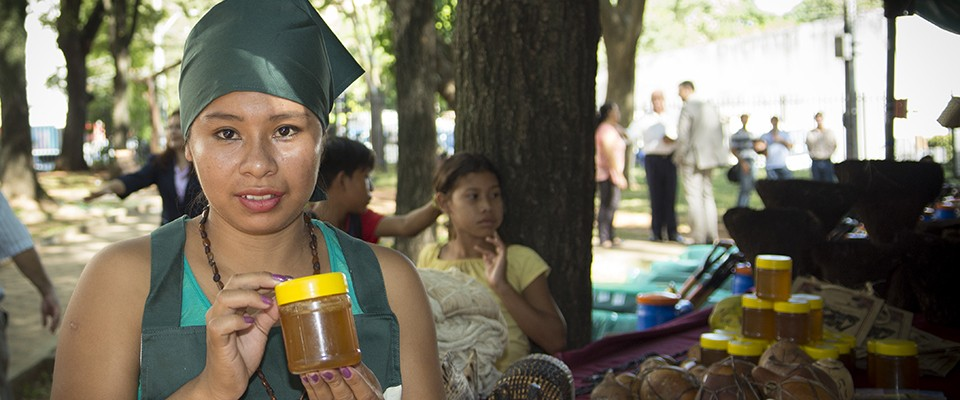 Indigenous woman selling honey at a local market - Credit: Teresa Torres for USAID