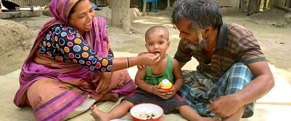 Feroza Begum with her husband feeds her young child