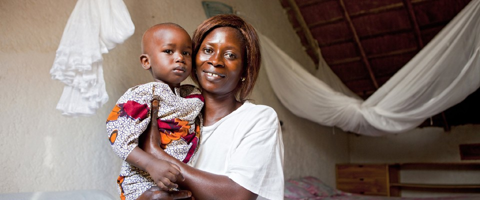 A mother holds her child. A mosquito net hangs in the background.