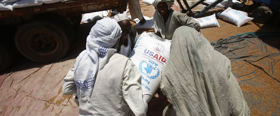 Workers at Port Sudan unload sorghum provided by USAID for people in need in Sudan. AFP Photo-Ashraf Shazly