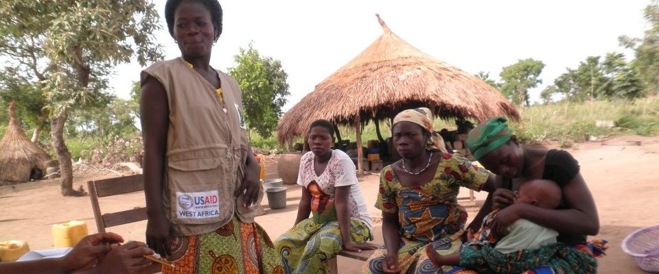 A community health worker speaks with three women and their babies outdoors.