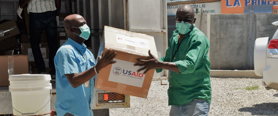 Men unload a box labeled with the USAID logo