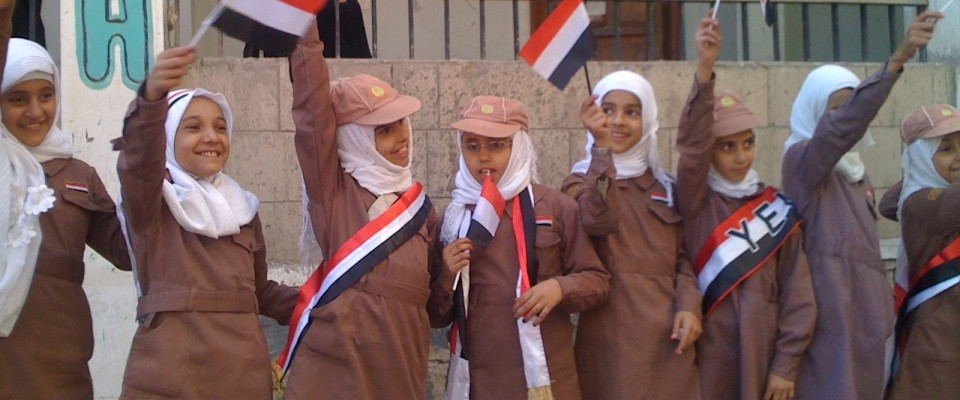 school girls hold flags in Yemen