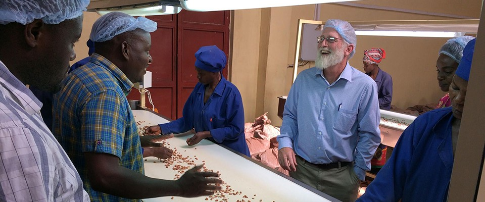 USAID Acting Mission Director Thomas Crubaugh learns about sorting of groundnuts after they are shelled during a tour of a Community Markets for Conservation (COMACO) factory.  For the past six years, USAID has supported COMACO through the Better Life Alliance Project (2012-2017), Partnering for Innovation Project (2017-2018), and Africa RISING research.