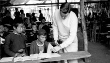 Meo tribe children and Hal Freeman, right, look at textbooks provided by USAID in Laos. In the background, a parachute serves as