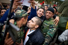 Tunisian protesters kiss soldiers during a demonstration against the presence of the toppled ruling party in the transitional go