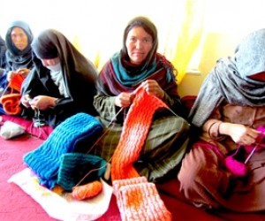 Khadeeja, one of the women who is receiving training on making quality cashmere clothing, knits a scarf.