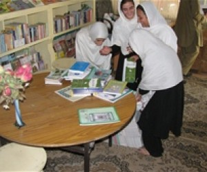 Girls at Fatima Balkhi Girls' High School in Mazar-e-Sharif happily unpacking books recieved through USAID funds.