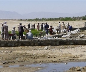 Residents improving an irrigation canal in Mehterlam District. This project will help to improve the arid land seen in the backg