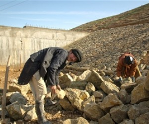 Islamuddin, 25, breaks large rocks to build part of a water reservoir to collect and harvest rain water. He is one of almost 6,0