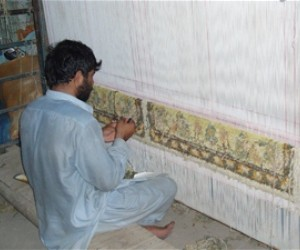A weaver weaves carpet for ZRM Carpet Company