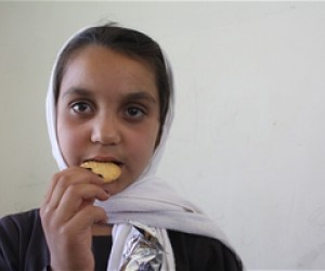 Sana, a third grader at a school in Kabul province, eats her first high energy biscuit.
