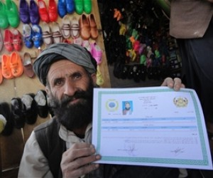 The owner of a shoe shop in Shahjoy proudly displays his newly acquired business license