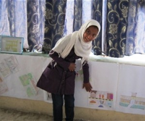 Zahra, a 6th grade student at Alikhel girls' school in Kapisa Province, proudly displays her award-winning drawing.