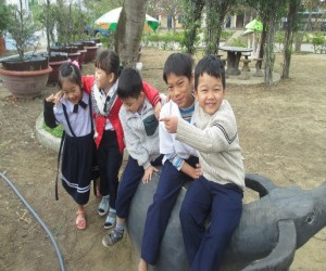 Tho (second right) plays with some of his new friends at the Pham Hong Thai primary school where he was enrolled with the help o