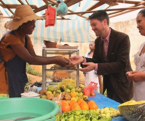 Christopher La Fargue, a USAID Food For Peace officer, buys fruit at Honorine's food stand