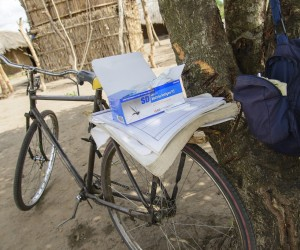 José Azevedo's bicycle is standing against a tree, with a local straw hut in the back suggesting one of Azevedo's health visits.