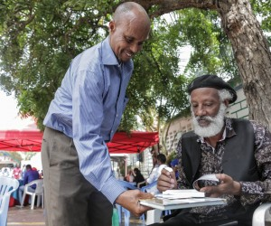 Abdilatif Ega, a renowned international author at the Mogadisihu Book Fair, signs a copy of his novel 'Guban.'