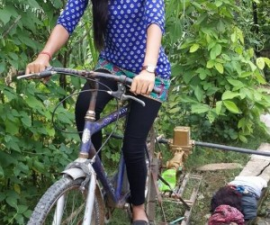 USAID trainee pumps water by riding a bike in Banke, Nepal.