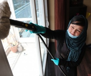 Aqela Faiz Ahmad, a housecleaner employed by Shahre Safa, dusts a window at a client's house.