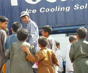 Excited children mill around the Badghis Ice Production Factory the day it opened