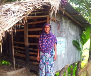 Photo of beneficiary and her chicken coop started with funds saved