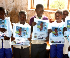 Students hold their new bed nets at Tanga Primary School.