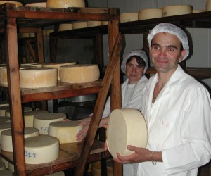 A man holds a block of cheese in a cheese storage facility
